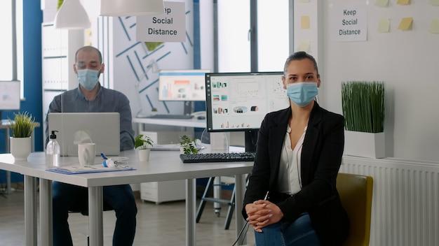 新しい通常の会社のオフィスに立っている間、医療用フェイスマスクを着用しているマネージャーの女性の肖像画。 covid19を回避するために社会的距離を尊重するマーケティングプロジェクトのバックグラウンドで働いている同僚