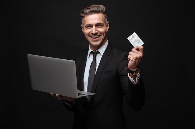 Портрет мужественного улыбающегося бизнесмена, одетого в формальный костюм, держащего портативный компьютер и кредитную карту, изолированную над черной стеной