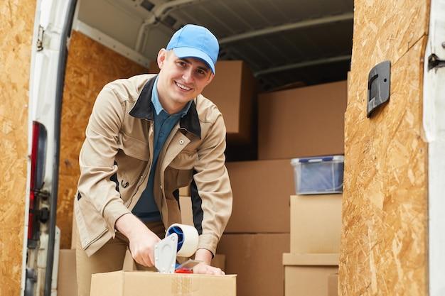 Портрет рабочего, улыбаясь в камеру, упаковывая коробки в фургон