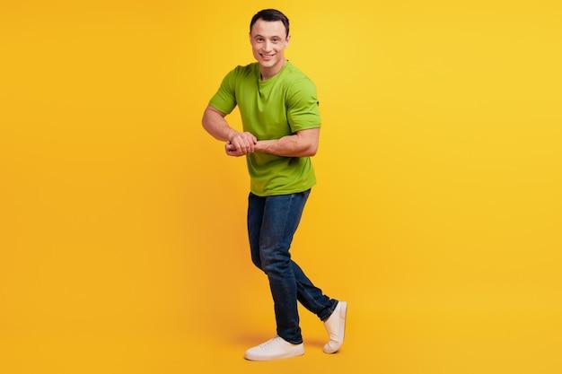 黄色の背景にショーの筋肉のポーズをとって男性的なスポーティな男の肖像画