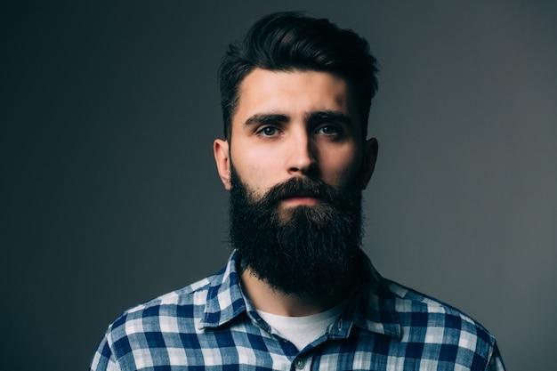 男らしさの肖像画。灰色の壁に立っている間ハンサムな若いひげを生やした男の肖像画
