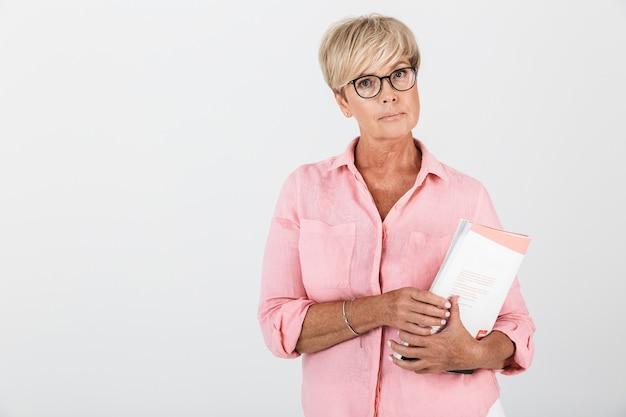 Портрет зрелой взрослой женщины в очках, держащей учебную книгу, изолированную над белой стеной в студии