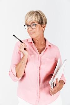 Портрет зрелой взрослой женщины в очках, держащей учебные книги и ручку, изолированную над белой стеной в студии
