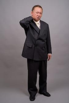 Портрет зрелого азиатского бизнесмена на сером фоне