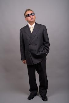 灰色の壁に対する成熟したアジアの実業家の肖像画