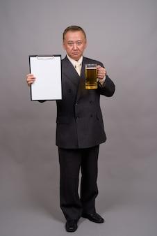Портрет зрелого азиатского бизнесмена против серой стены