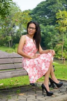 屋外の公園でリラックスした成熟したアジアの女性の肖像画