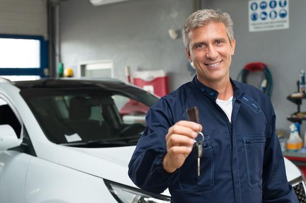 Портрет зрелого автомеханика в гараже, держа ключ от машины