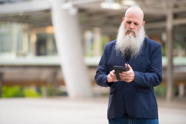 야외 도시의 거리에서 긴 수염을 가진 성숙한 대머리 사업가의 초상화