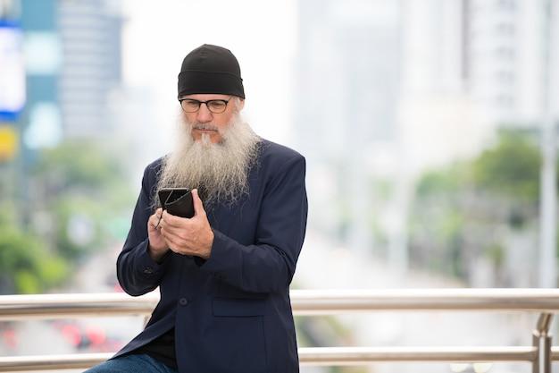 야외 도시 거리에서 안경을 쓰고 긴 수염을 가진 성숙한 대머리 사업가의 초상화
