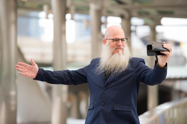 屋外の街の通りで眼鏡をかけている長いひげを持つ成熟したハゲの実業家の肖像画