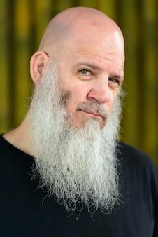 Портрет зрелого лысого хипстера с длинной бородой у бамбуковой стены на открытом воздухе