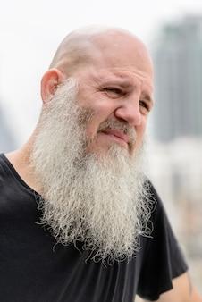 Портрет зрелого лысого хипстерского мужчины с длинной бородой на фоне города на открытом воздухе