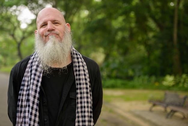 Портрет зрелого лысого битник с длинной бородой в парке на открытом воздухе