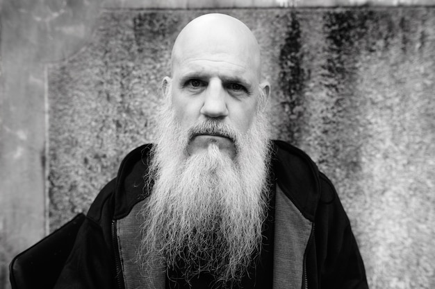 흑인과 백인 야외에서 그런 지 콘크리트 벽에 긴 회색 수염을 가진 성숙한 대머리 남자의 초상화