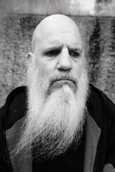黒と白の屋外のグランジコンクリート壁に対して長い灰色のひげを持つ成熟したハゲ男の肖像画
