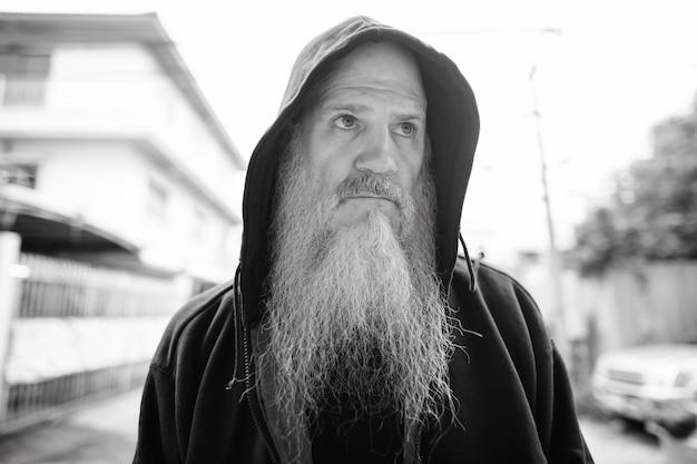 Портрет зрелого лысого мужчины с длинной седой бородой на улице на улице в черно-белом