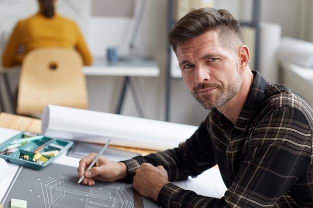 청사진 및 사무실에서 드로잉 책상에 앉아 계획을 작업하는 동안 성숙한 수염 건축가의 초상화,