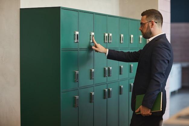 オフィスやコワーキング、コピースペースでロッカーを開く成熟したひげを生やしたビジネスマンの肖像画