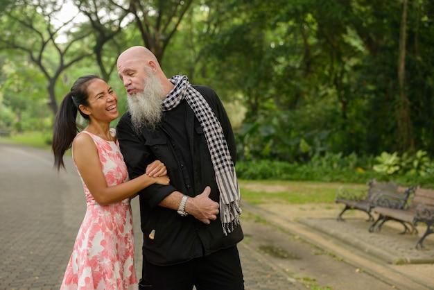 Портрет зрелого бородатого мужчины и зрелой азиатской женщины как супружеская пара