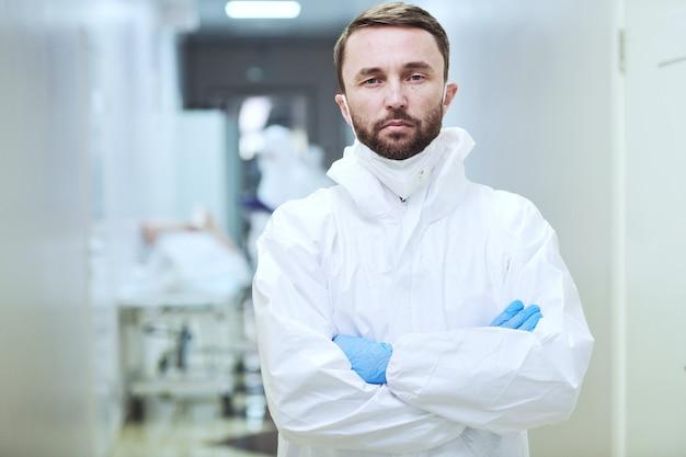 病院で腕を組んで立っているカメラを見て保護服を着た成熟したひげを生やした男の肖像画