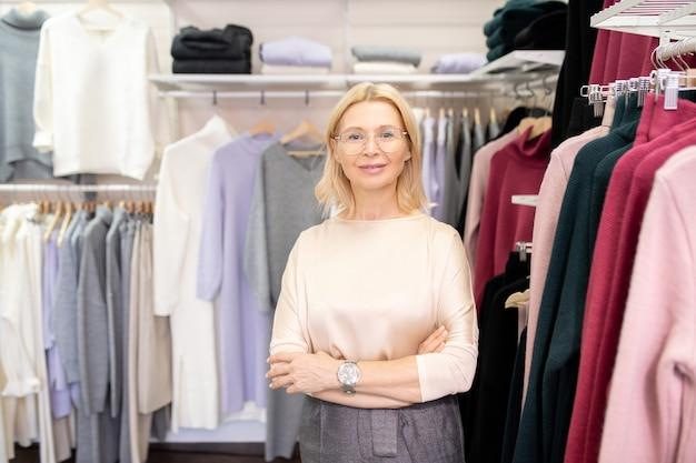 衣料品店に立って顧客を待っている間カメラに微笑んで成熟した美しいセールスウーマンの肖像画