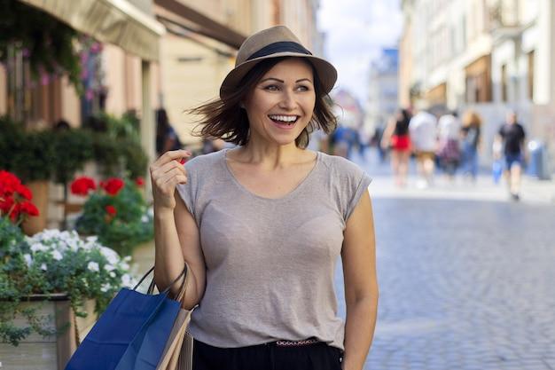 ショッピングバッグ、都市のライフスタイル、都会的なスタイル、コピースペースと帽子の成熟した美しい成功した笑顔の女性の肖像画