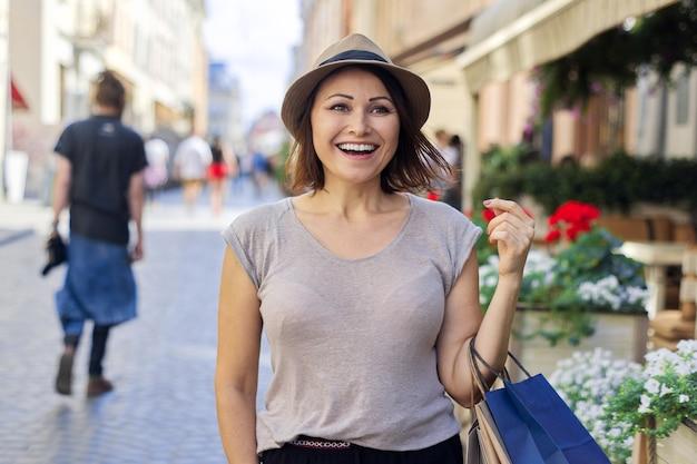 ショッピングバッグ、都市のライフスタイル、都会的なスタイルの帽子で成熟した美しい成功した笑顔の女性の肖像画