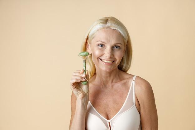 Портрет зрелой блондинки с идеальной светящейся кожей, улыбающейся в камеру с нефритовым лицом