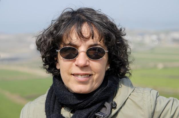 Портрет зрелой брюнетки в солнцезащитных очках