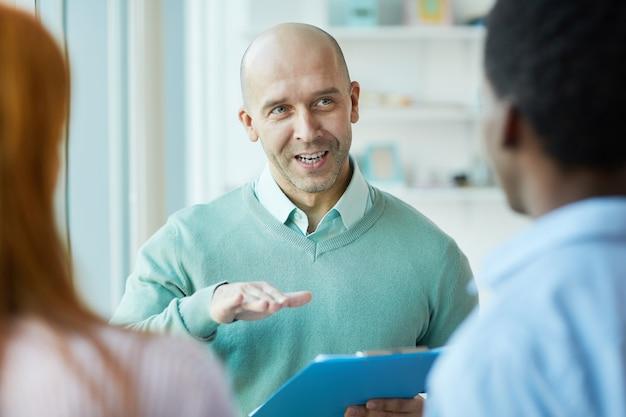 オフィスでのインターンシップ中に若い研修生に指示する成熟したビジネスマネージャーの肖像画、コピースペース