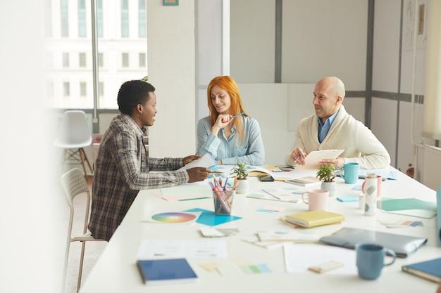 現代の白いオフィス、コピースペースでのインタビュー会議中にアフリカ系アメリカ人のインターンと話している間元気に笑っている成熟したビジネスマンの肖像画