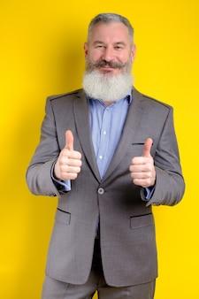 灰色のスーツに身を包んだ成熟したビジネスマンの肖像画は親指を示しています