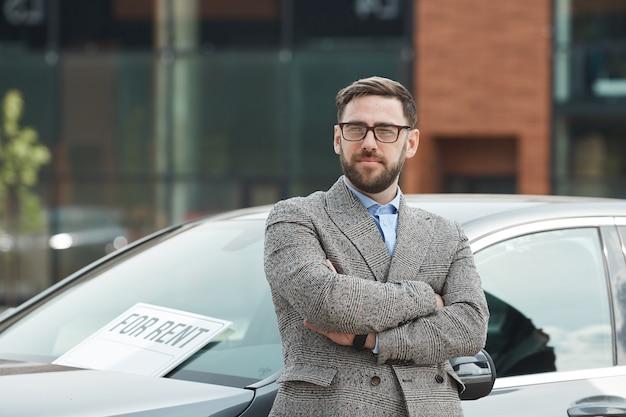彼は車を借りて運転している屋外で腕を組んで立っている眼鏡の成熟したビジネスマンの肖像