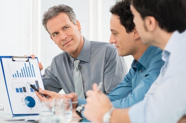 Портрет зрелого бизнесмена, показывающего график годового отчета своим коллегам