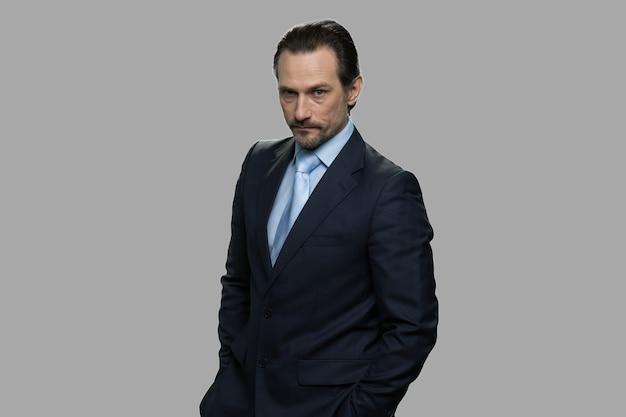 怒った顔で成熟したビジネスマンの肖像画。灰色の背景に深刻な不快な上司。人間の表現と感情。