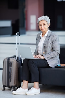 Портрет зрелой деловой женщины, смотрящей во время работы на ноутбуке в аэропорту