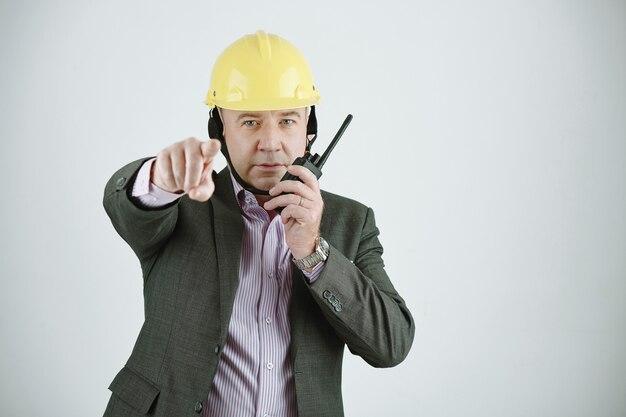 무전기를 통해 통신하는 동안 카메라를 가리키는 안전모를 쓴 성숙한 건설 관리자 또는 건축가의 초상화