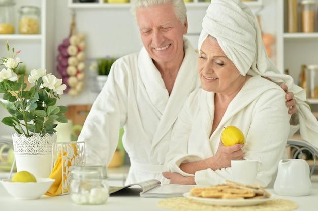 キッチンでバスローブを着た成熟したカップルの肖像画