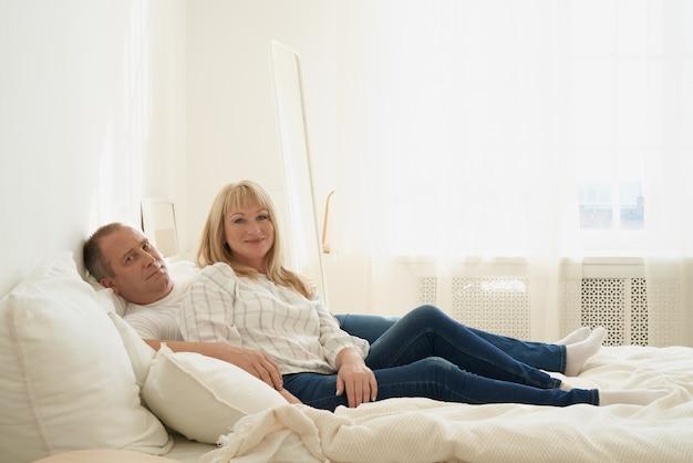 Портрет зрелой пары в домашнем интерьере на диване