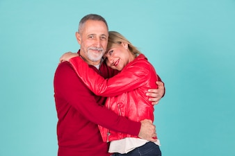 Portrait of mature couple standing against turquoise background