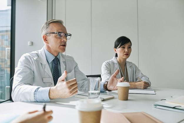의료 세미나 중에 연설하는 동안 회의실의 회의 테이블에 앉아 있는 성숙한 의사의 초상화