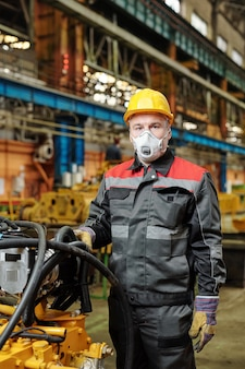 기계 장비 근처에 서 있는 동안 카메라를 보고 마스크를 쓴 성숙한 엔지니어의 초상화