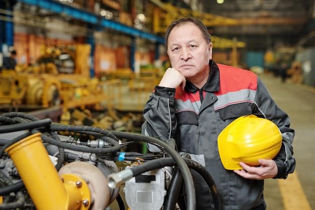 기계 공장에서 일하는 카메라를 바라보는 작업복을 입은 성숙한 엔지니어의 초상화