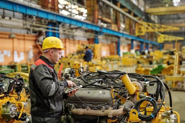 Портрет зрелого инженера в спецодежде, смотрящего на камеру, работающую на машиностроительном заводе