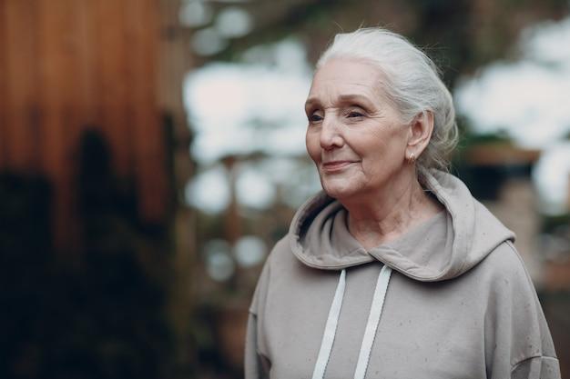 Портрет зрелой седой пожилой пожилой женщины на открытом воздухе