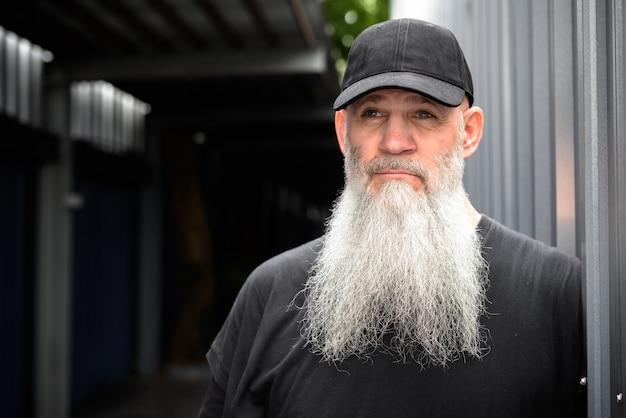 街の成熟したハンサムなひげを生やした流行に敏感な男の肖像画