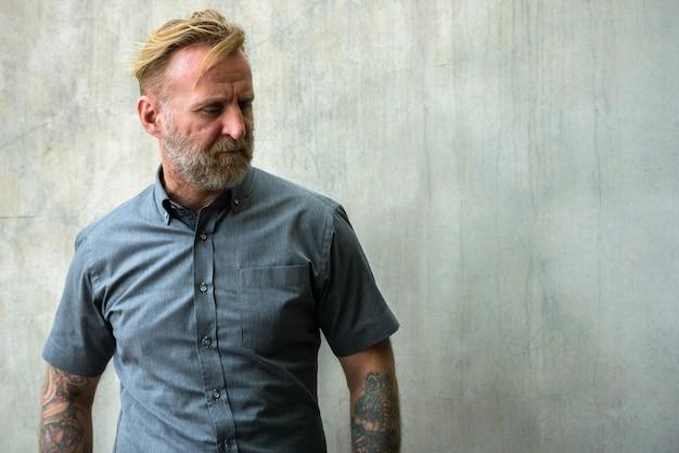 Портрет зрелого красивого бородатого мужчины с татуировками рук у бетонной стены на открытом воздухе