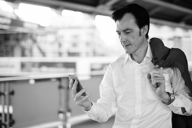 Портрет зрелого красивого бизнесмена, исследующего город в черно-белом