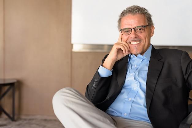 Портрет зрелого красивого латиноамериканского бизнесмена в офисном здании в помещении